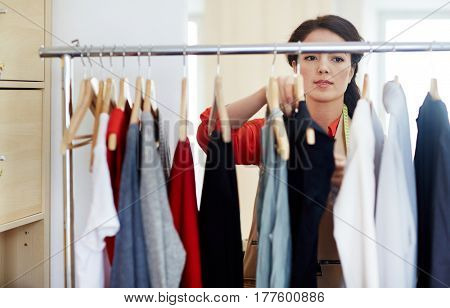 Owner of dressmaking studio looking through clothes