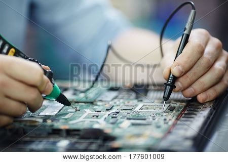 Closeup shot of male hands testing electric current voltage in circuit board of disassembled laptop using multimeter tool on table in maintenance shop poster