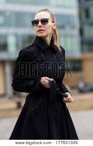 Beautiful girl in a cloak and black glasses on the background of the city