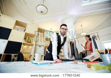 Serious man leaning at his workplace in fashion studio