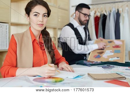 Young fashion designer and her colleague working in studio