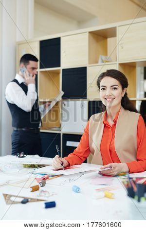 Stylish female looking at camera while working in fashion studio