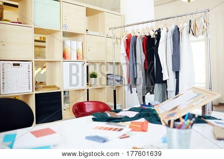 Workplace of fashion designer and rail with stylish clothes near by