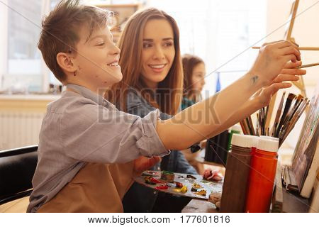 Teaching young generation. Cheerful smiling young teacher sitting in the art studio and conducting class while teaching children and expressing happiness