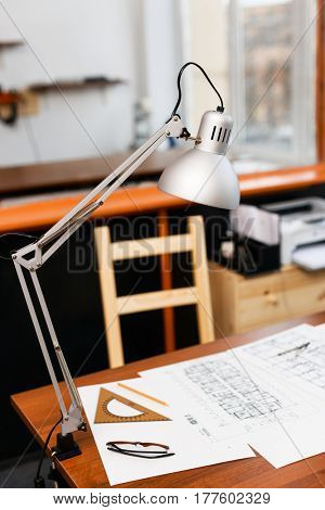 Lamp, measuring tool and sketch of construction on desk
