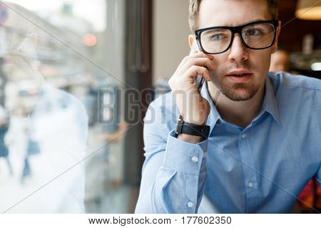 Young man in eyeglasses and formalwear talking on cellphone