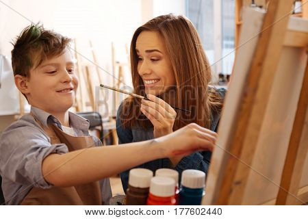 Happy family weekend. Smiling cheerful happy mother sitting at home and painting with her son while having fun and smiling