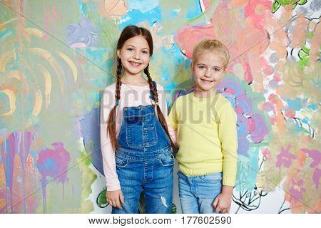 Little friendly girls in casualwear standing against creative wall
