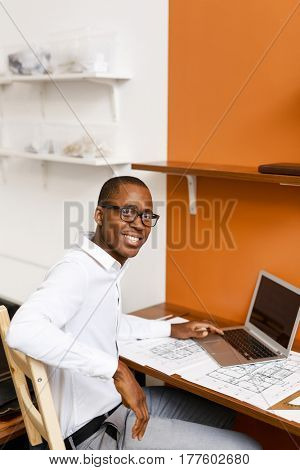 Mobile engineer with laptop looking at camera at workplace