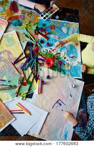 Hands of kids with paintbrushes painting big picture