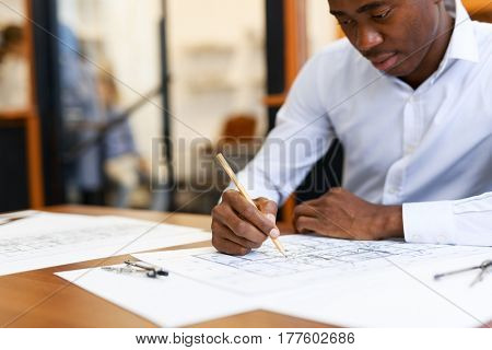 Young specialist sketching plan of new construction project
