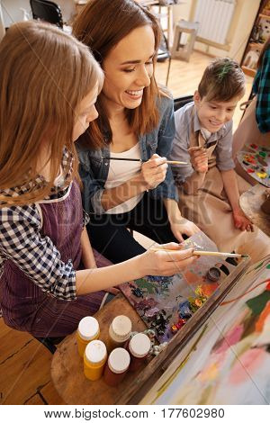 Mastering new skills. Smiling inventive young artist sitting in the studio and conducting art class while teaching children painting