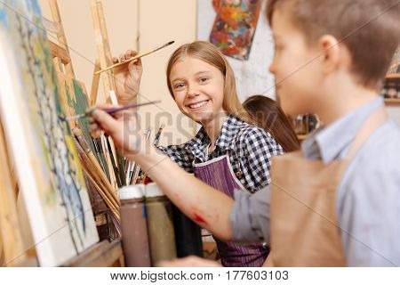 Joyful art lesson. Smiling delighted playful kids sitting in the studio and having painting lesson while expressing joy and holding paintbrushes