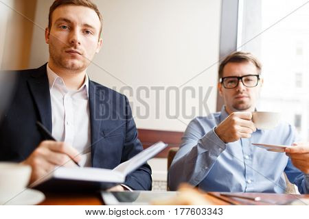 Serious employer making notes in notepad on background of colleague