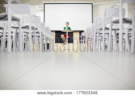Young businesswoman sitting by whiteboard in lecture-room