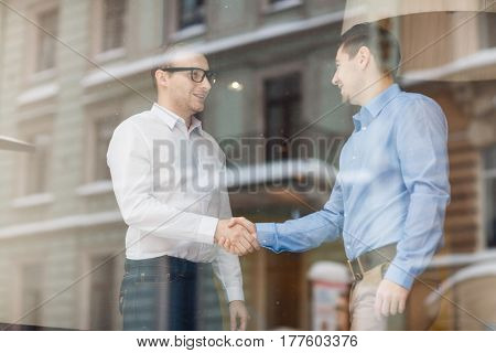 Confident traders handshaking after discussing terms of contract