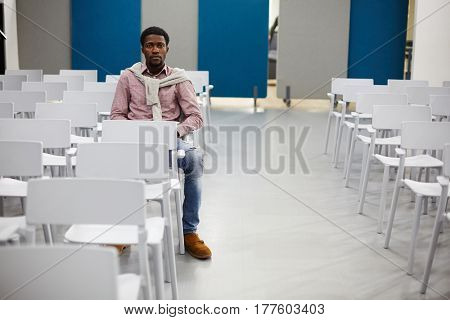 Serious student sitting on chair in empty conference-hall