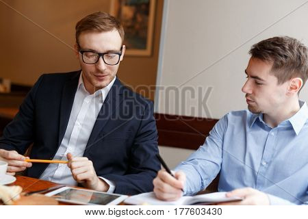 Small group of confident co-workers discussing financial data