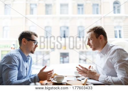 Young analysts having conversation by business lunch in cafe