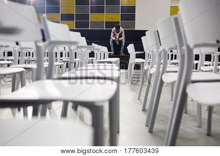 Pensive student sitting in conference-hall