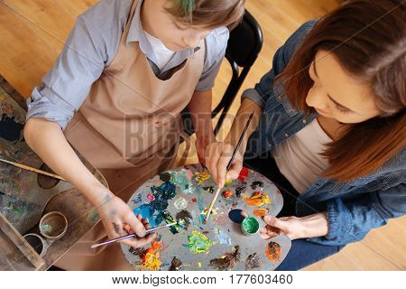 Creating masterpiece together. Proficient involved experienced painter sitting in the studio and conducting art class while teaching child painting