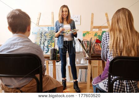 Studying art together. Proficient smiling cheerful painter standing in the studio and holding pallet while teaching children