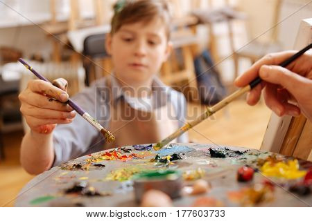 Using colorful pallet . Proficient skillful helpful artist standing in the studio and holding pallet while teaching child and mixing tones