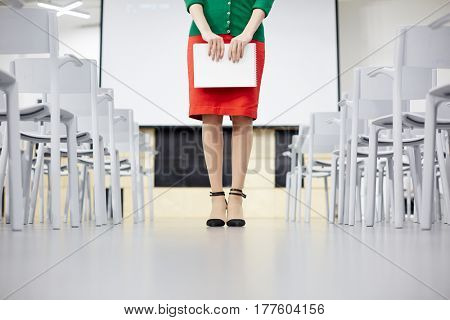 Low section of teacher in red skirt inside lecture-room
