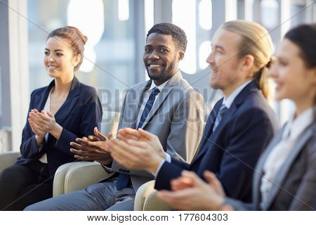Multi-ethnic group of smiling business people sitting in row in modern glass hall and clapping, focus on cheerful African businessman looking at camera