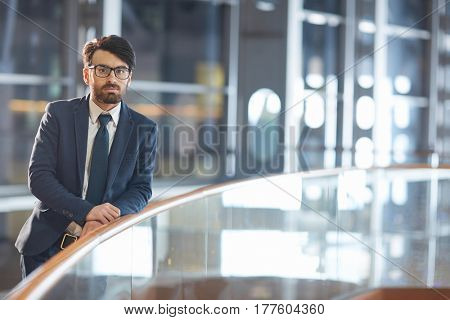 Portrait of confident Middle Eastern businessman wearing glasses. Standing leaning on glass railing and looking at camera in modern hall of night time office building