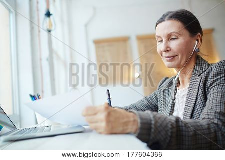 Aged female listening to music in earphones while reading paper