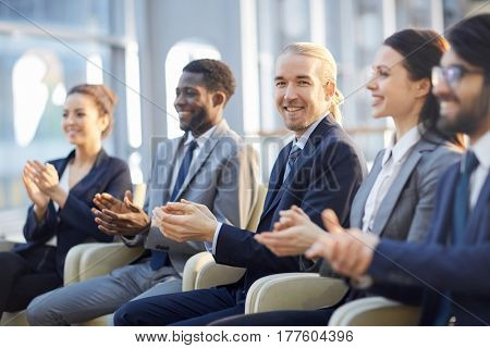 Multi-ethnic group of smiling business people sitting in row in modern glass hall and clapping, focus on young cheerful  businessman in center