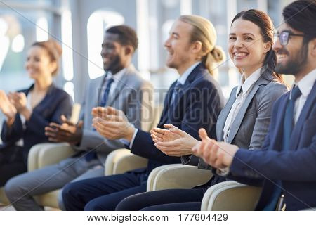 Multi-ethnic group of smiling business people sitting in row in modern glass hall and clapping, focus on beautiful brunette businesswoman looking at camera