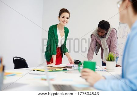 Happy manager consulting with co-worker while preparing for conference