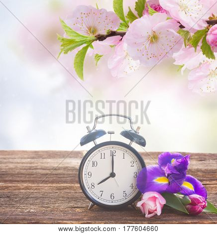 Spring time concept - retro alarm clock with fresh flowers on wooden shelf