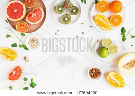 Colorful fresh fruit on white table. Orange tangerine lime kiwi grapefruit. Summer fruit. Flat lay top view copy space