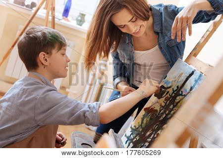 Enjoying art lesson . Delighted positive skilled teacher standing in the school and expressing joy while teaching painting child