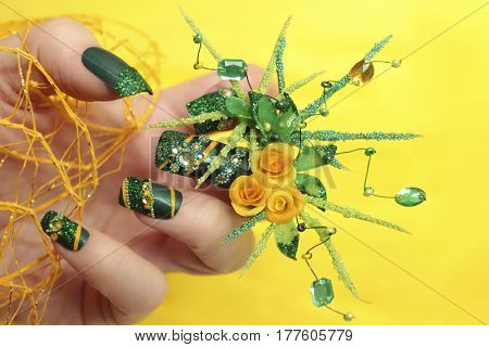 Design green acrylic nails with yellow roses and green petals handmade with sequins,beads,with rhinestone closeup.High art.Nail art.