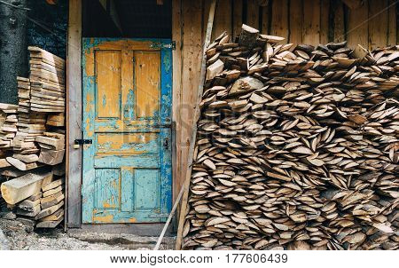 View at a village storage house for tools and fire woods. Vintage painted door in blue color. Paint is partially pilled off. Fire woods stored under a roof near a storage village house.