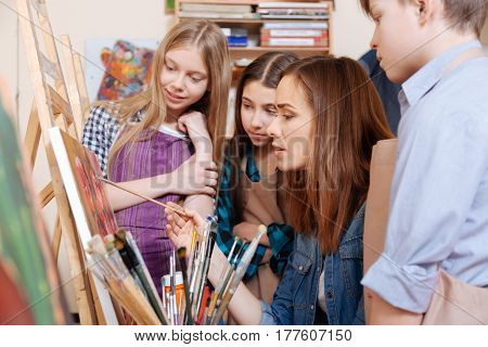 Teaching gifted generation. Concentrated positive skilled artist sitting in the art studio and expressing interest while teaching painting kids