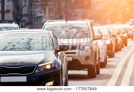 Close-up of the lane of cars in traffic jam against the sun