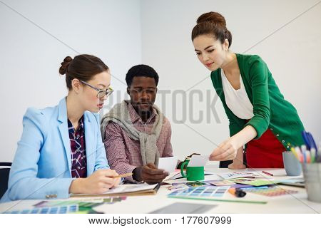 Creative businesspeople looking at photos and discussing them