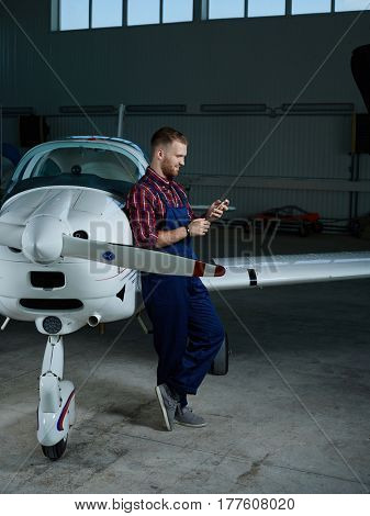 Technician with smartphone leaning at air-vehicle and messaging
