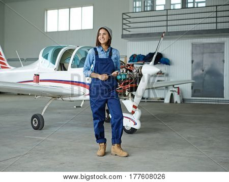 Young woman with wrench standing in hangar by jetliner