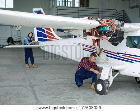 Young man and woman repairing jetliner