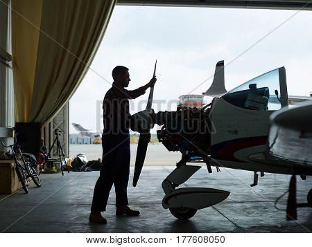 Outline of repairman checking up turbine of jetliner