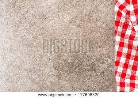Red checkered tablecloth on the stone background. copy space