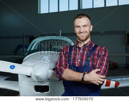 Handsome mechanic in uniform standing by new airplane