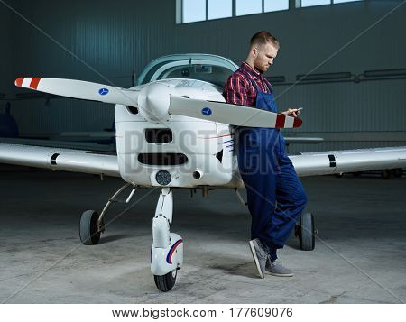 Serious engineer texting in smartphone while standing by airplane in hangar