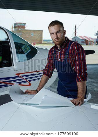 Repairman of jetliners with blueprint looking at camera